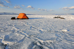 Bicycle tourists' winter camp. – orange tent and bikes on the surface of frozen lake in morning light royalty free stock photo