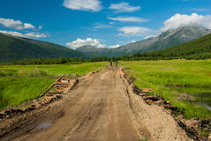 Bicycle tourists on the bumpy road. Two bicycle tourists riding by the bumpy gravel road throw the swamp to mountains Stock Photography