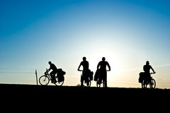 Bicycle tourists silhouette. Group of Bicycle tourists on a road against sunset stock photography
