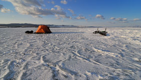 Bicycle tourists winter camp. – orange tent and bikes on the surface of frozen lake in morning light stock images
