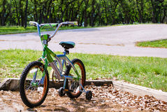 Bicycle with Training Wheels in the Park. A bicycle with training wheels sitting in the park Royalty Free Stock Photos