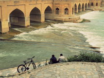 A bicycle and two friends enjoy Isfahan riverside by old bridge Royalty Free Stock Photography