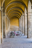 Bicycle under the arches. A bicycle under the arches along the street in Lucca - Tuscany Royalty Free Stock Image