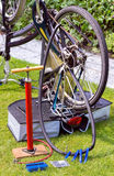Bicycle upside down flat tire repair. Bicycle upside down on grass outside for flat tire reparation royalty free stock photography