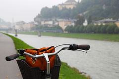 A bicycle on a view of a park, a river and mountains. Royalty Free Stock Photos