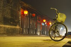 Bicycle in Village. Night time street scene in a small village in Western China with a vintage bicycle in the foreground Royalty Free Stock Photo