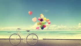 Bicycle vintage with heart balloon on beach blue sky Royalty Free Stock Image