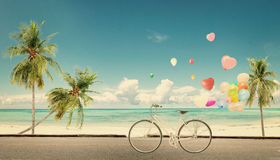 Bicycle vintage with heart balloon on beach blue sky Stock Image