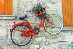 Bicycle on a wall with flowers in a basket Stock Photography