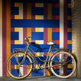 Bicycle on a wall full of geometric pattern. Vintage bicycle on a wall full of geometric pattern Stock Photos