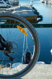 Bicycle wheel and boats. Part of bicycle wheel with boat harbour in the background. Boats intentionally out of focus Stock Photos