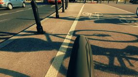Bicycle wheel and cyclist shadows on the city bike path Stock Images
