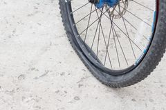 Bicycle wheel with flat tyre on the concrete road. Stock Photos