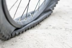 Bicycle wheel with flat tyre on the concrete road. Royalty Free Stock Images
