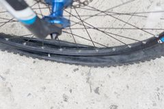 Bicycle wheel with flat tyre on the concrete road. Stock Image
