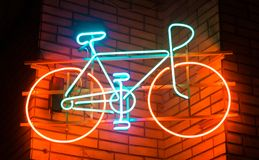 Bicycle wheel neon transportation on a brick wall royalty free stock image
