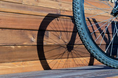 Bicycle wheel with shadow from wheel on wooden boards Stock Photography