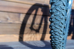 Bicycle wheel with shadow from wheel on wooden boards Royalty Free Stock Photo