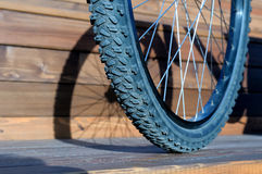 Bicycle wheel with shadow from wheel on wooden boards Stock Images