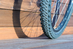 Bicycle wheel with shadow from wheel on wooden boards Stock Image