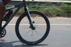 Bicycle wheels rotate at high speeds on the road and blur. Stock Photos