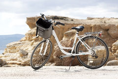 Bicycle. White bicycle with bag on rocky background Stock Photo