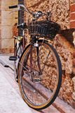 Bicycle with a wicker basket with old brick walls Royalty Free Stock Photography