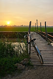Bicycle on wooden fence of bridge at sunset Royalty Free Stock Images