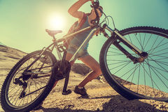 Bicycle. Young lady climbing up the sandy hill with a bicycle in the desert at sunny day Royalty Free Stock Images