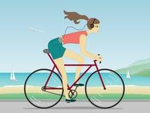 Bicycleand Reiten der jungen Frau, das Musik hört Stockfoto