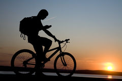 Bicycler with phone. Bicyclist on bicycle call phone a background of the  sunset Stock Images