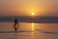 A bicycler rides into the sunset on Cox Bay in Tofino, BC. A person rides a bike on the beach as the sun sets behind them on Cox bay, Tofino, BC stock images