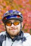 Bicycler sonriente joven en el fondo del otoño Fotos de archivo libres de regalías