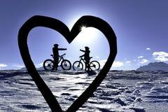 Bicyclers μέσω της σκιαγραφίας καρδιών στοκ φωτογραφίες