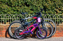 Family bicycles chained to wall. Three family bicycles parked beside a  wall Royalty Free Stock Photo