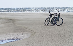 Bicycles on the Beach. Two bicycles parked on an ocean beach Royalty Free Stock Photos