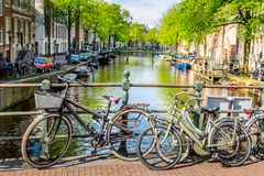 Bicycles on the bridge in Amsterdam, Netherlands against a canal during summer sunny day. Amsterdam postcard iconic view. Tourism. Concept stock image