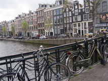 Bicycles and canal houses in Amsterdam Stock Photos