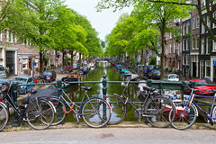 Bicycles chained to bridge. Characteristic view of an Amsterdam, the Netherlands, canal with Holland's ubiquitous bicycles chained to a bridge on a Spring Royalty Free Stock Photo