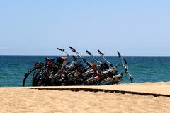 Bicycles on a golden sandy beach of Barcelona with turquoise blue water. Bicycles chained together and parked by tourists on the sandy beach of Barcelona with stock photos