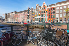 Bicycles and colorful houses along canal in spring sunny day Stock Photos