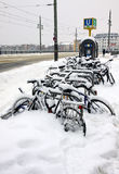 Bicycles covered with a snow parked on the street Stock Images