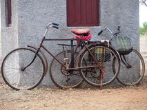 Bicycles Of Cuba. Old model bicycles with red seats against a grey wall Cuba Royalty Free Stock Photography