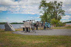 Bicycles cycling tourists leaning on a bench by the river Stock Photo