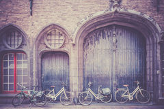 Bicycles leaning against old wooden door Royalty Free Stock Photography