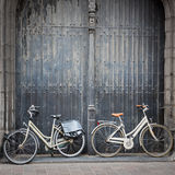 Bicycles leaning against old wooden door Stock Photos