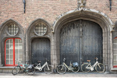 Bicycles leaning against old wooden door Stock Images