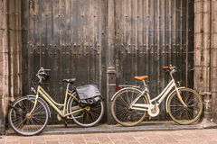Bicycles leaning against old wooden door Stock Photography