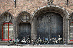 Bicycles leaning against old wooden door Stock Image
