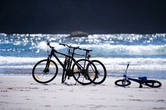 Bicycles for the whole family are waiting for cyclists on the Pa. Bicycles of the mother of father and child are on the shore of the Pacific Ocean, the waves of Stock Photo